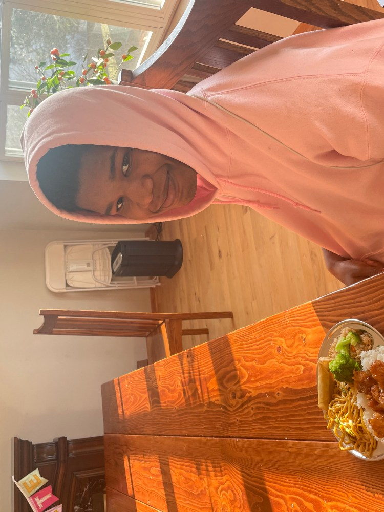 Jaxen, a tall Black boy wearing a pink hoodie, sitting at a long table with a plate of Chinese food in front of him. He is smiling for the camera.