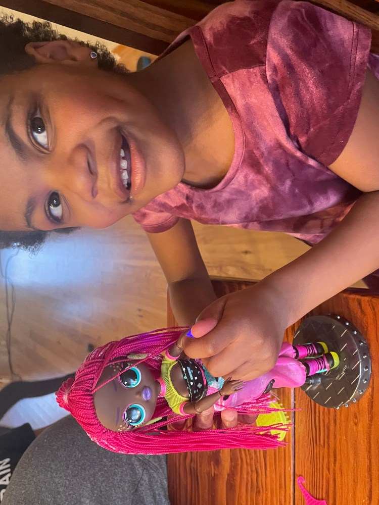 Isabel, a small Black girl in a dark purple dress, with her doll. The doll has long, pink, braided hair. Isabel is holding the doll for the camera to see.