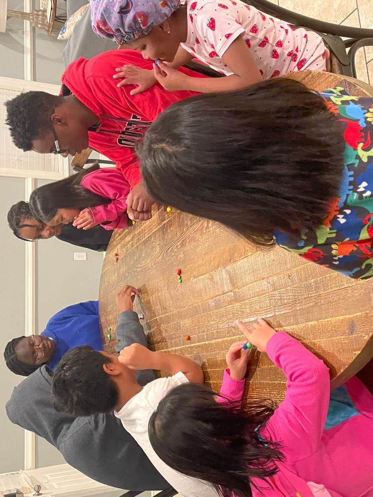 A family is gathered around a long table, they are playing a game with dice, each person has a few small pieces of candy in front of them.