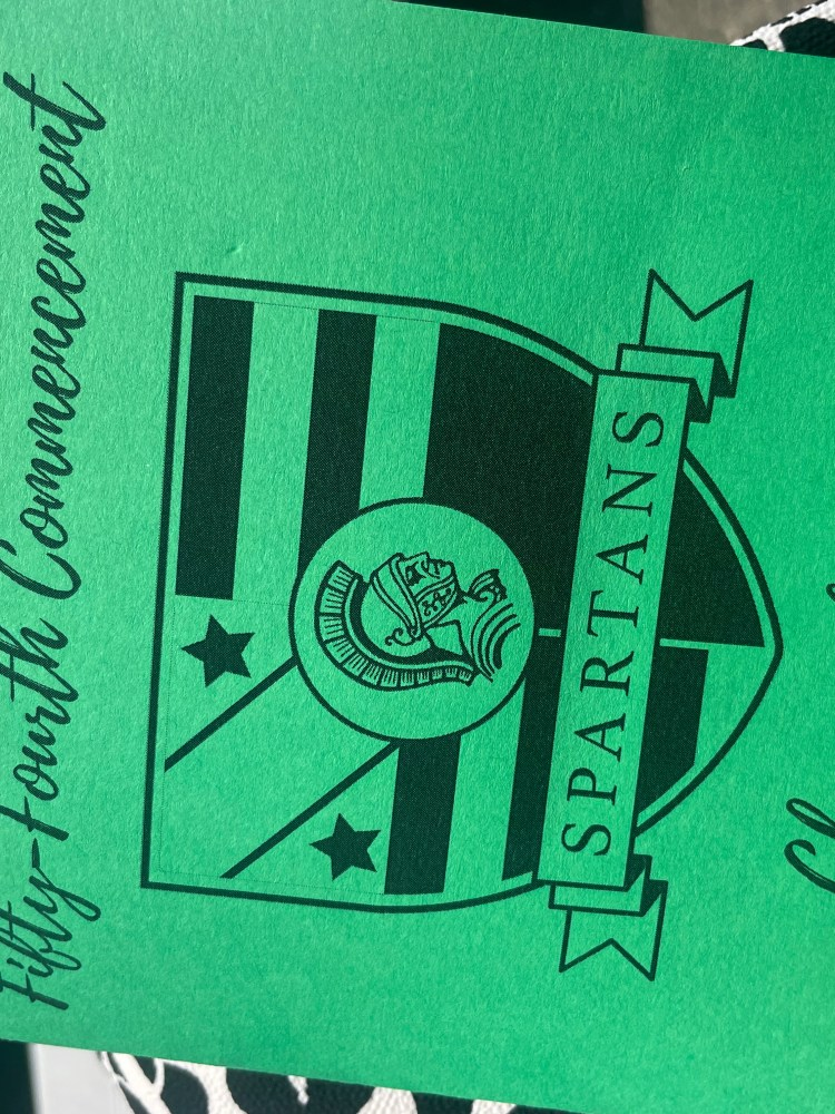 Image of the front of a graduation program. The program is printed on green paper. The black lettering reads 'James Madison Memorial High School. Fifty-Fourth Commencement. Spartans. Class of 2021.'