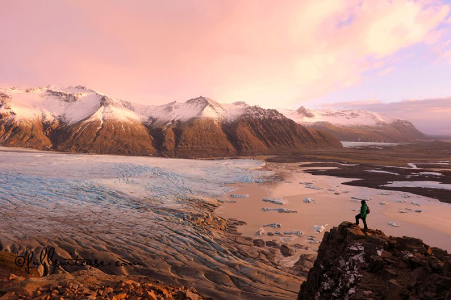 Hiker standing on a cliff at a glacier in Skaftafell National Park Iceland at sunset in winter