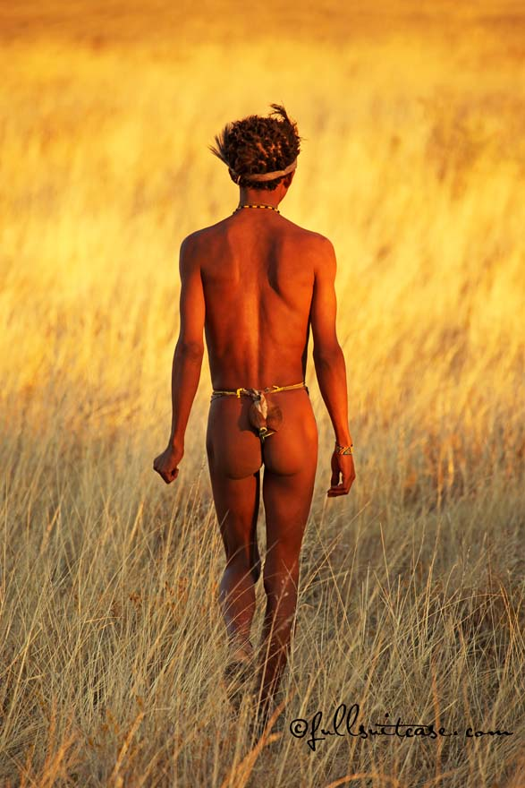 Male San hunter is walking in African savannah at sunset
