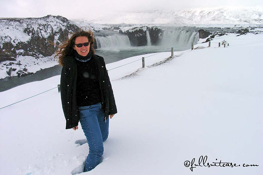 Tourist standing in knee-high snow at a waterfall in Northern Iceland