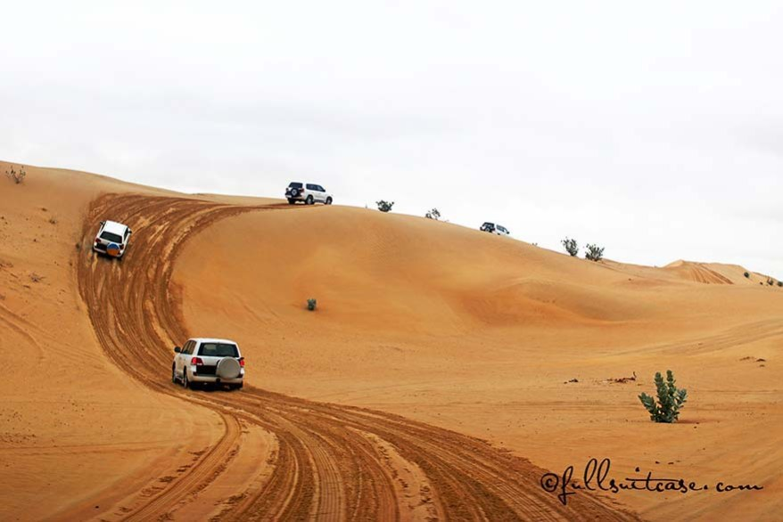 Group of 4x4 vehicles driving in a desert in Dubai