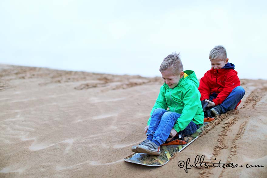 Dubai family activities - kids sand boarding in the desert