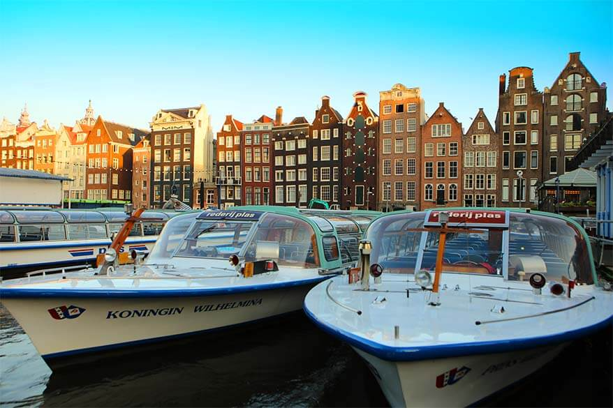 Damrak boats and historic buildings in Amsterdam