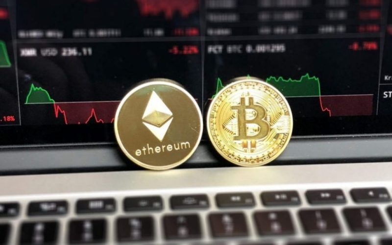 Physical Cryptocurrency Bitcoin and Ethereum on a laptop
