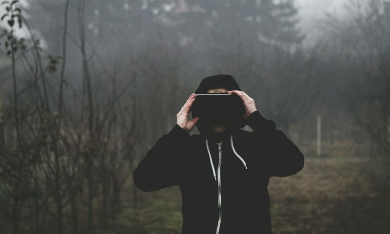 Man standing outdoors wearing a black hoodie and a Virtual Reality headset