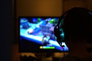 Cheating Kid playing video game with headset on likely a streamer, possibly playing to relieve stress