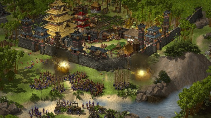Stronghold: Warlords gameplay showing the use of gunpowder in two locations outside a wall