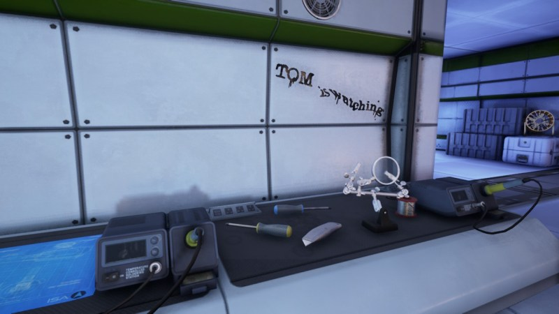 """The Turing Test work bench with message """"Tom is watching"""" scrawled on the wall"""
