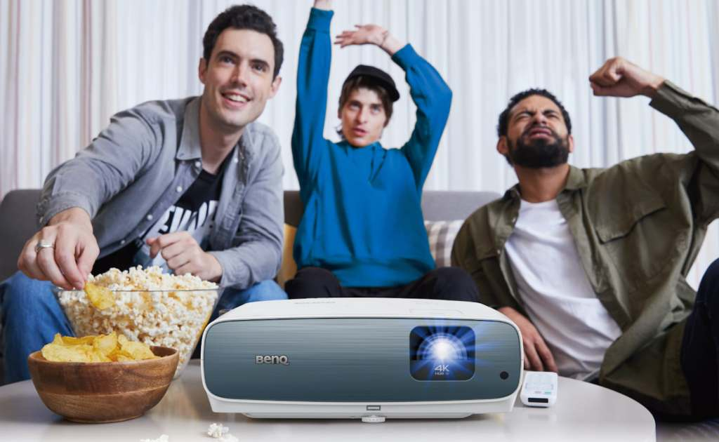 BenQ TK850 on table next to popcorn with people watching the screen