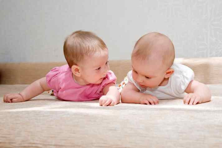 two babies are looking at the floor