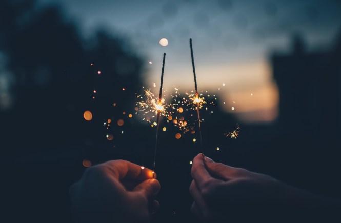 Hände mit Leuchtstäben zu Silvester