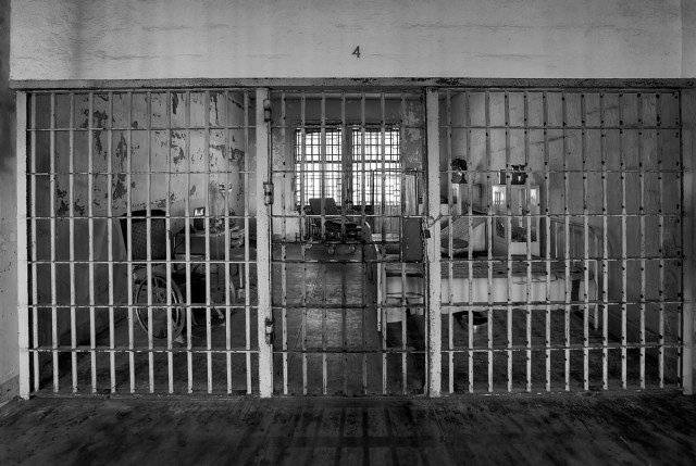 black and white photograph of a prison hospital ward through the bars