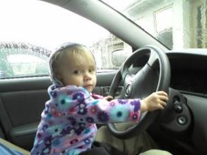 my two-year-old daughter pretending to drive our car