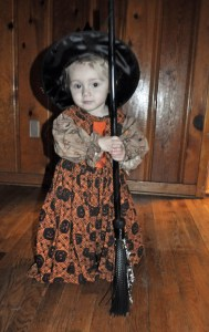 toddler girl in a witch Halloween costume holding a black broom