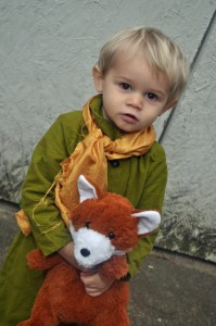 toddler in The Little Prince Halloween costume holding a stuffed animal fox