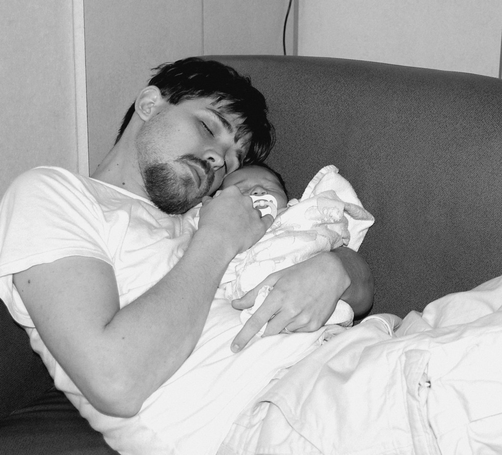 Black and white photo of my husband holding our newborn daughter.
