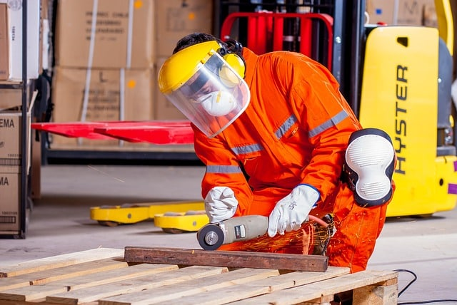 Worker with safety attire on cutting steel