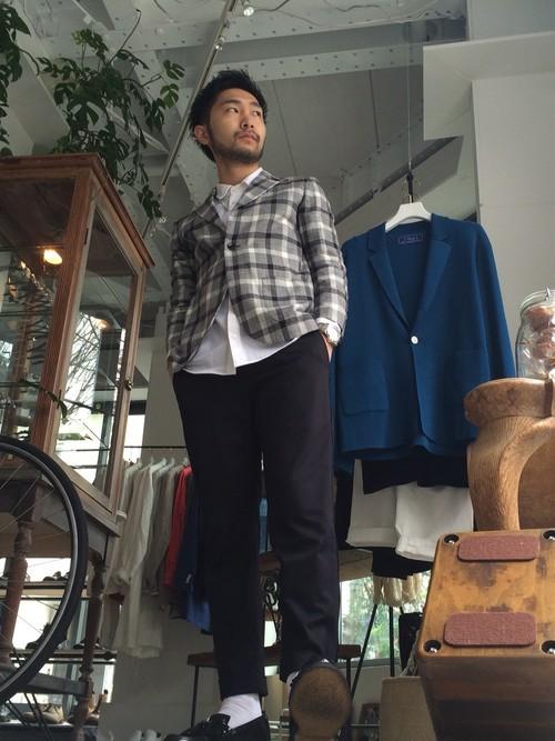 シャツ生地のジャケットに黒スラックスを合わせた男性の着こなし