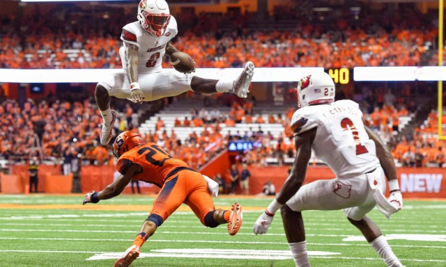 Sep 9, 2016; Syracuse, NY, USA; Louisville Cardinals quarterback Lamar Jackson (8) leaps over Syracuse Orange defensive back Cordell Hudson (20) during the second quarter at the Carrier Dome. Mandatory Credit: Rich Barnes-USA TODAY Sports ORG XMIT: USATSI-269760 ORIG FILE ID:  20160909_krj_ai8_102.JPG