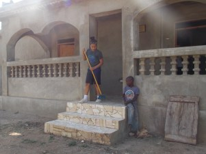 One of our students sweeping the steps of the kitchen building