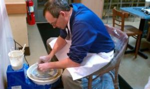 Pottery Classes - Man throwing a pot on a potters wheel.