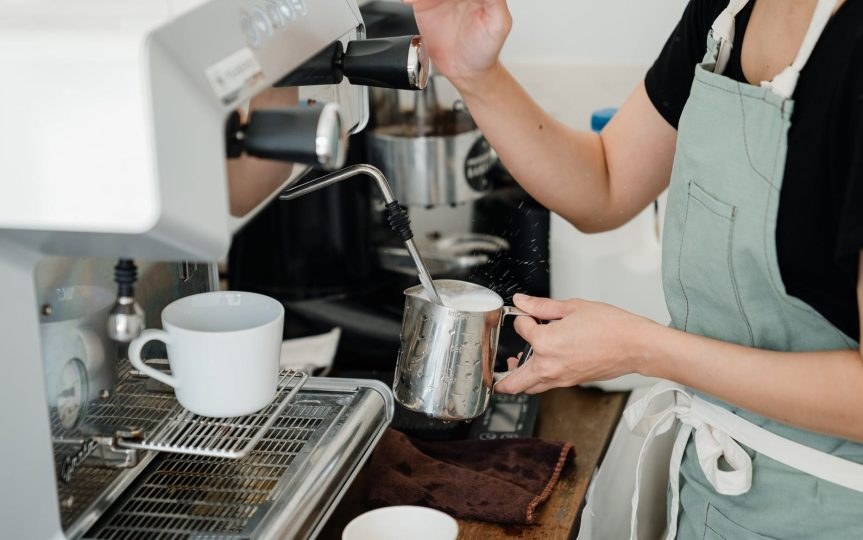 crop young woman making frothed milk in coffee shop