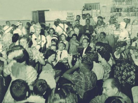 """Carnaval – 1956 Flagrante dos foliões no Bar Ponto Chic. Em vários locais de Varginha se realizavam as festas carnavalescas. Entre eles o Clube de Varginha, o Clube Infantil (antigo Pio XII), a Boate Corujinha e a Radio Clube. Os desfiles na Av. Rio Branco eram prestigiados por grande parte da população. Entre aqueles que desfilavam estavam a Escola de Samba Hora H; o bloco feminino """"Garotas do Universo""""; o bloco misto """"Pierrots"""" e o bloco masculino """"Apaches"""". O Bar Ponto Chic era localizado na esquina da rua Presidente Antônio Carlos com Wenceslau Brás, onde hoje fica a loja Magazine Luíza. Muito frequentado na década de 40 e 50, seu proprietário era Antônio Augusto Pinto."""