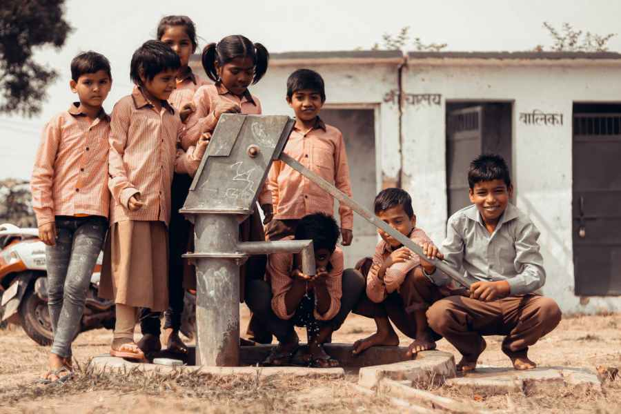 children standing next to manual water pump