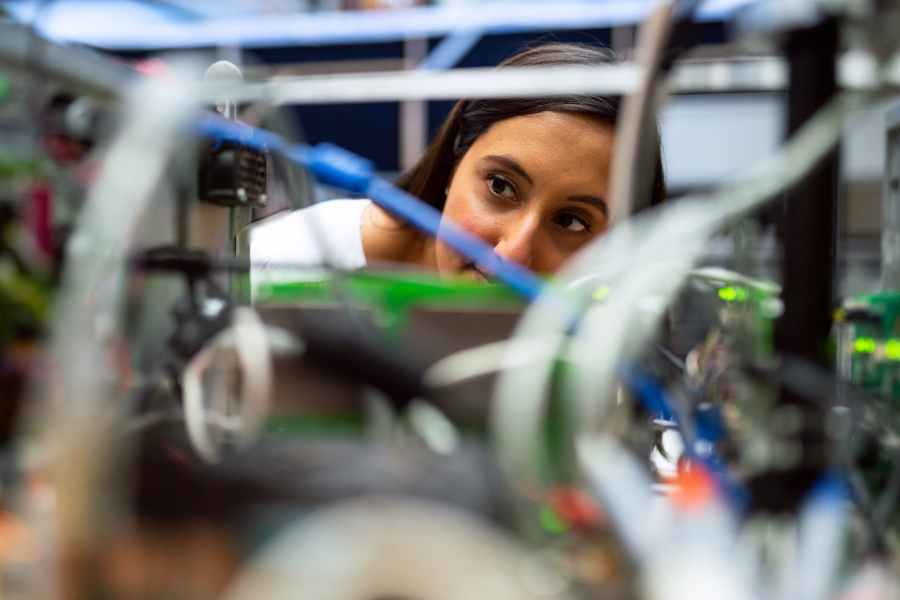 photo of female engineer looking through wires