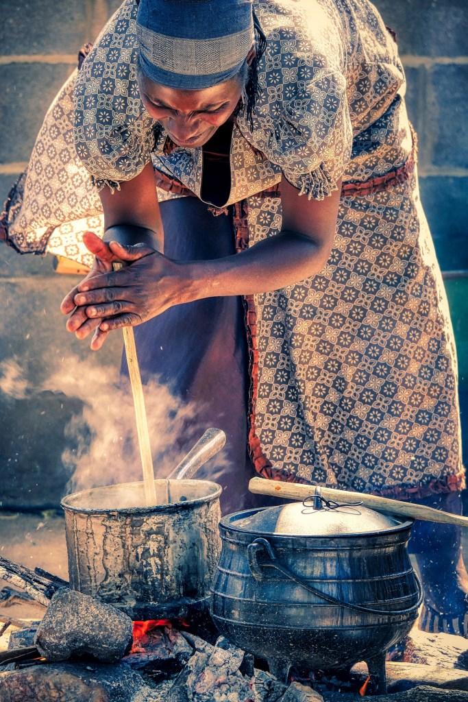 Mujer cocinando con fuego en África