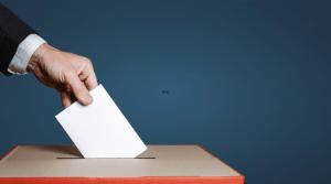 Mano de una persona ingresando un voto a una urna