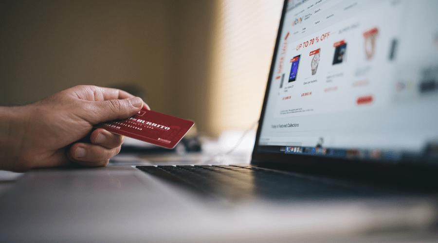 Muestra una mano con una tarjeta de crédito frente a un computador
