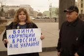 """Jekatierina Maldon trzyma transparent """"Wojna korupcji w Rosji, a nie Ukrainie"""""""