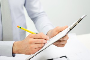business, people and paperwork concept - close up of businessman hands writing to clipboard at office