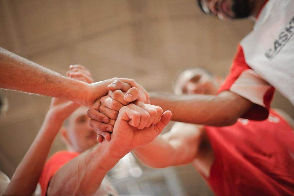 group of 4 people put their hands in before a game