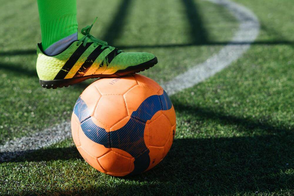yellow cleat stands on orange soccer ball