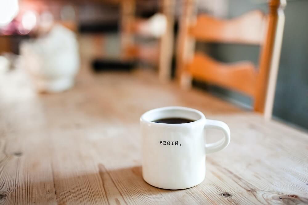 coffee mug that says begin on it.