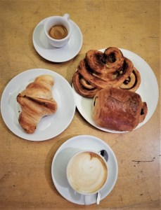 two coffees, croissant, cinnamon and chocolate pastry