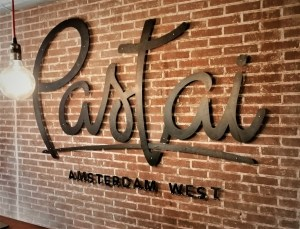 Black Pastai sign on the restaurant wall