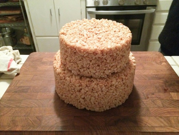 stacking the layers of the Rice Krispie treat cake
