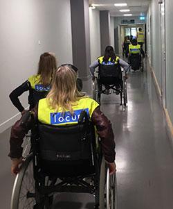 Flera personer i rullstol åker på rad genom en lång korridor