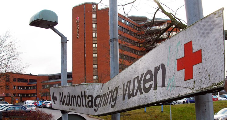 En bucklig skylt med texten akutmottagning vuxen. I bakgrunden St Görans sjukhus.
