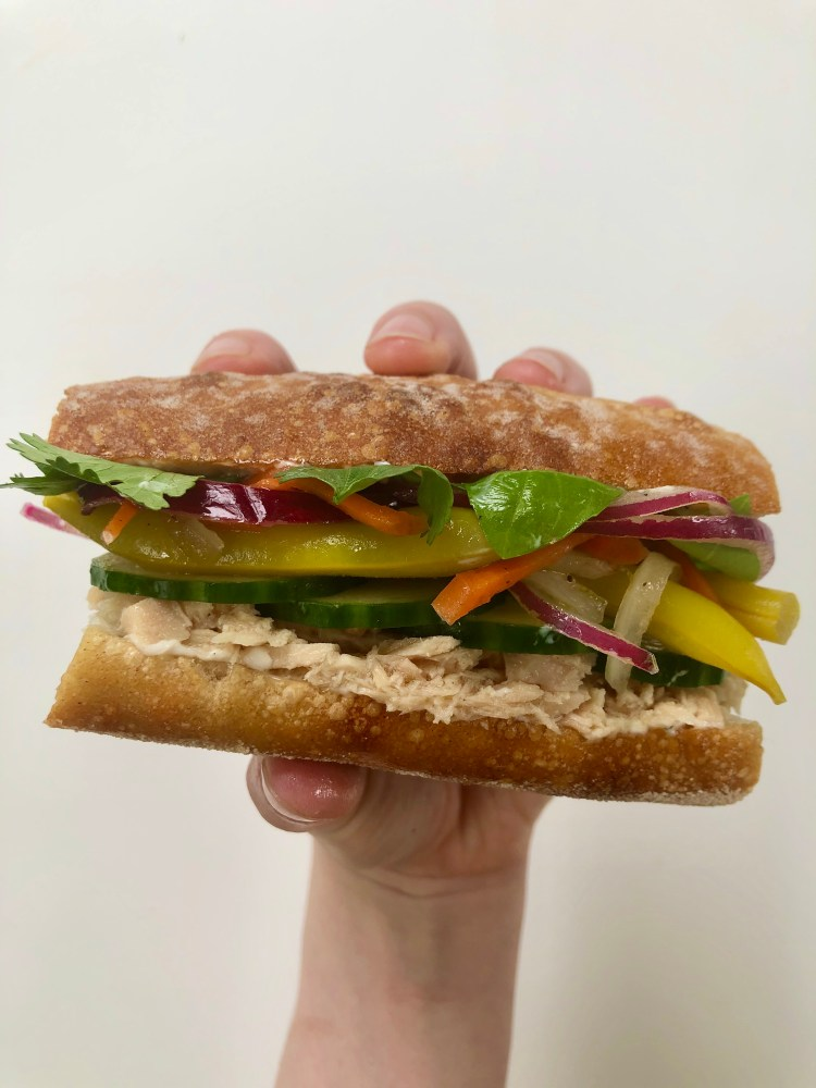 holding a Tuna Banh Mi Sandwich with Pickled Yellow Beans