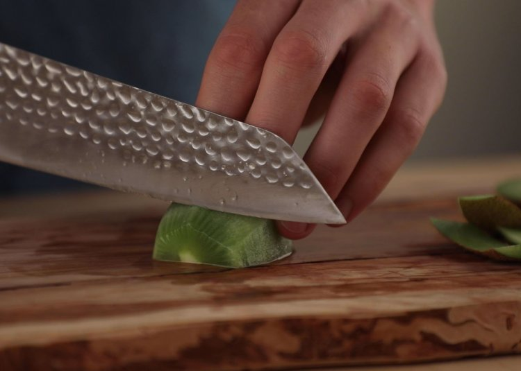 Kiritsuke Kotai Chef Knife slicing a kiwi