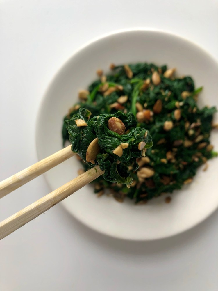 spinach salad with pumpkin seed oil held with chop sticks