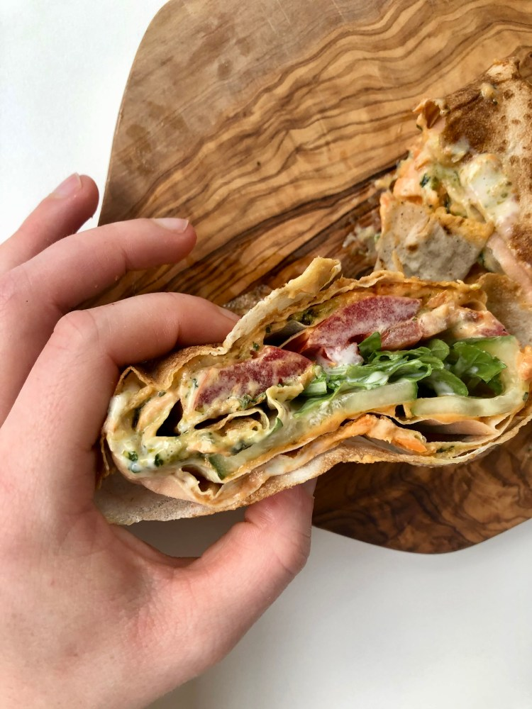 hand holding markouk sandwich wrap with vegetables and hummus