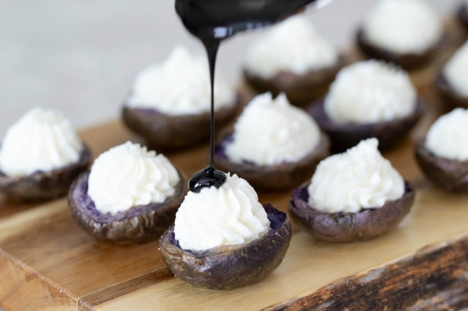 Drizzling balsamic vinegar over mini potatoes with goat cheese